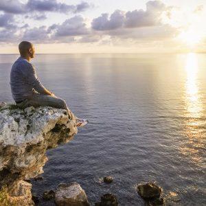 Man sitting on rock on seashore looking at sunset