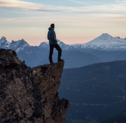 Man standing on precipice looking out to mountains in the distance