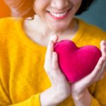 Smiling woman in yellow sweater holds red heart in her hands