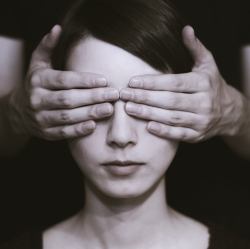 Brown tone picture of hands being held in front of a young woman's eyes