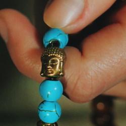 Hand holding turquoise mala with Buddha head bead